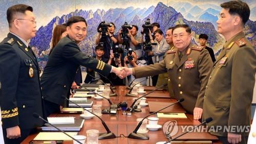 Le général de division Kim Do-gyun (à g.), chef de la délégation sud-coréenne de cinq membres, serre la main du général de corps d'armée An Ik-san (à d.), chef de la délégation nord-coréenne, le 31 juillet 2018, avant leurs pourparlers à la Maison de la paix, un bâtiment contrôlé par la Corée du Sud dans le village de Panmunjom situé dans la Zone démilitarisée (DMZ) séparant les deux Corées.