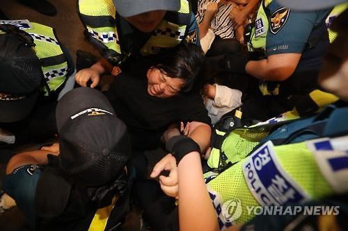 警察に連行される大学生ら=28日、ソウル(聯合ニュース)