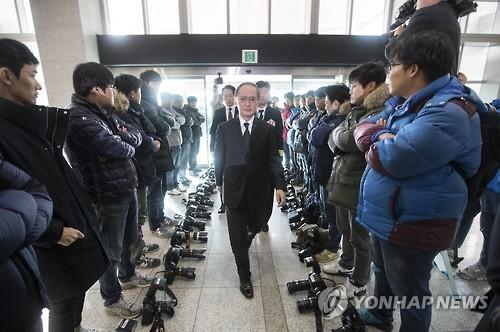 署名式の非公開に抗議し、長嶺大使(中央)が到着した際、カメラを地面に置いた写真記者ら