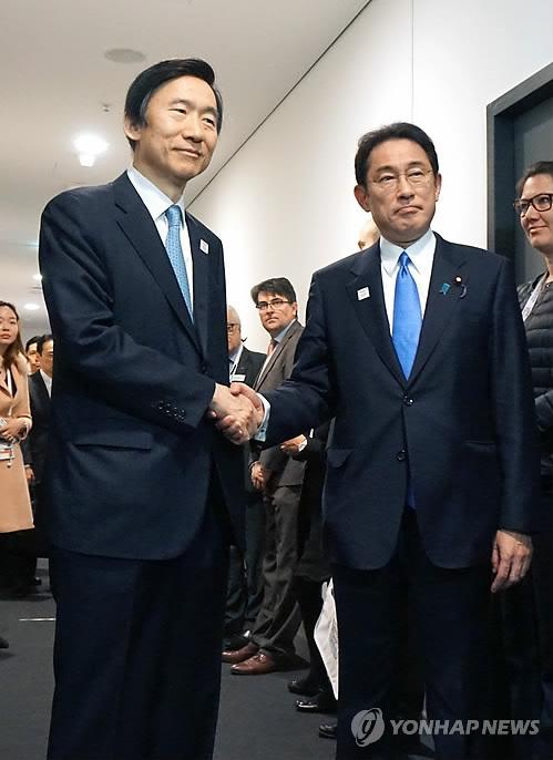 会談会場の外で握手する尹長官(左)と岸田外相=17日、ボン(聯合ニュース)