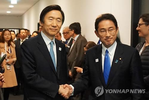 会談前に握手する尹長官(左)と岸田外相=17日、ボン(聯合ニュース)