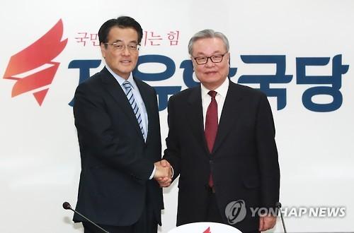 握手を交わす印氏(右)と岡田氏=20日、ソウル(聯合ニュース)