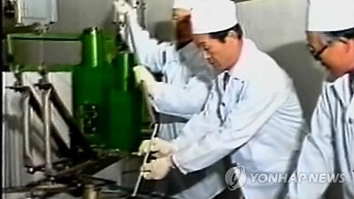 実験を行う北朝鮮の科学者=(聯合ニュースTV提供)