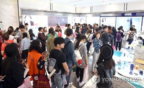 中国人観光客で混み合う免税店の化粧品売り場=(聯合ニュース)