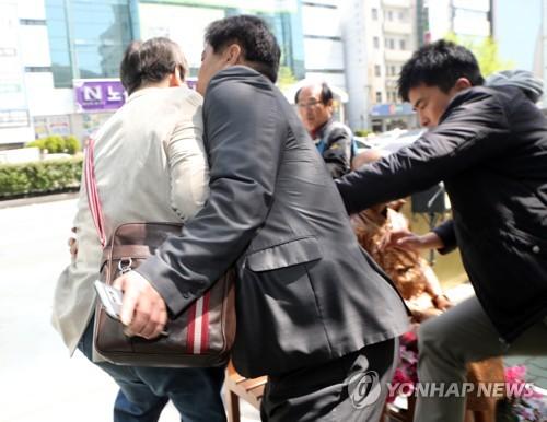 警察に阻止される男性(左端)=19日、釜山(聯合ニュース)