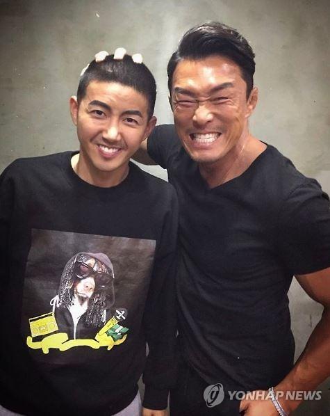 プロ格闘家、秋山成勲さん(右)が自身のインスタグラムに掲載した丸刈り頭のグァンヒさん=(聯合ニュース)