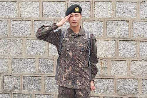 除隊後、報道陣の前で敬礼するユンホさん(SMエンタテインメント提供)=20日、ソウル(聯合ニュース)