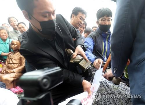 少女像設置に反対する団体の代表(左)=21日、釜山(聯合ニュース)