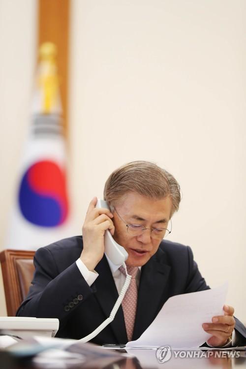 安倍首相と電話会談する文大統領(韓国大統領府提供)=11日、ソウル(聯合ニュース)