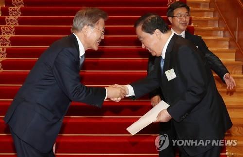 文大統領(左)から親書を受け取る文元国会副議長(青瓦台提供)=16日、ソウル(聯合ニュース)