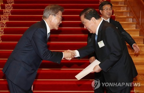 文大統領(左)から安倍首相に渡す親書を受け取る文元国会副議長(青瓦台提供)=16日、ソウル(聯合ニュース)