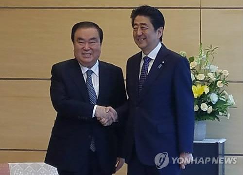 安倍首相(右)と握手する文喜相氏=18日、東京(聯合ニュース)