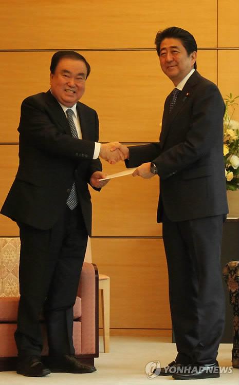 安倍首相(右)に文大統領の親書を渡す文特使=18日、東京(聯合ニュース)