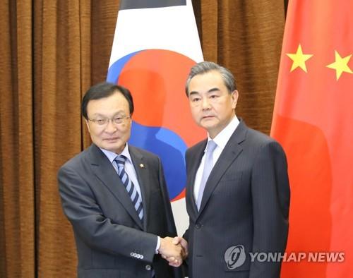 握手を交わす李特使(左)と王外相(共同取材団)=18日、北京(聯合ニュース)