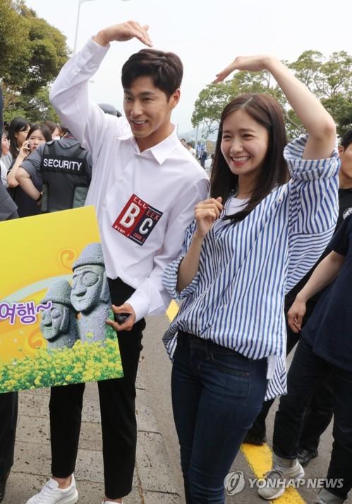 済州空港で開かれた電気自動車(EV)に関するイベントでポーズを取るユンホ(左)とユナ=19日、済州(聯合ニュース)