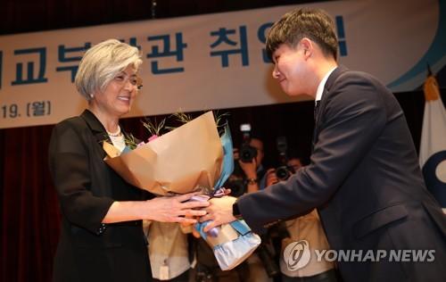 就任式で職員から花束を受け取る康氏(左)=19日、ソウル(聯合ニュース)