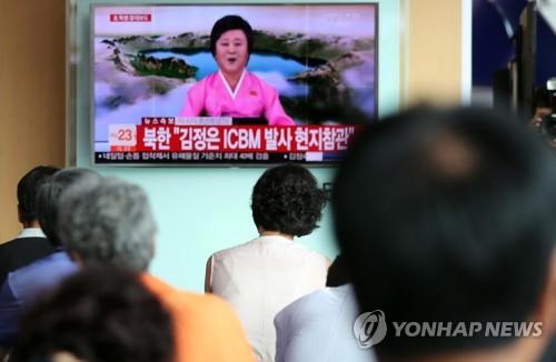 ソウル駅で北朝鮮の発表を報じるニュースを見つめる市民=4日、ソウル(聯合ニュース)