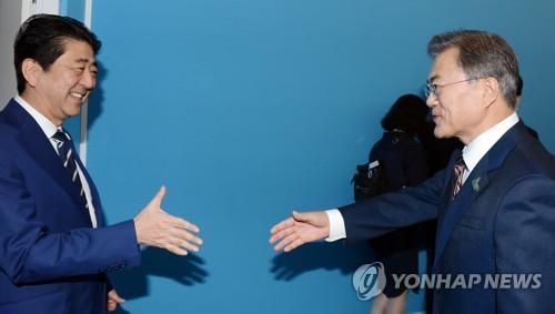 初めての首脳会談を行った安倍首相と文大統領=7日、ハンブルク(聯合ニュース)