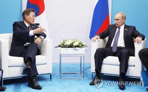 意見を交わす文大統領とプーチン大統領=7日、ハンブルク(聯合ニュース)