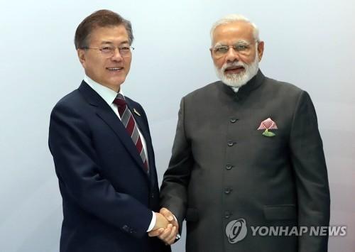 モディ首相(右)と握手する文大統領=8日、ハンブルク(聯合ニュース)