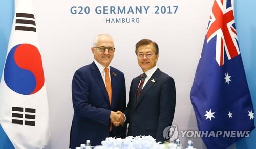 ターンブル首相(左)と固い握手を交わす文大統領=8日、ハンブルク(聯合ニュース)