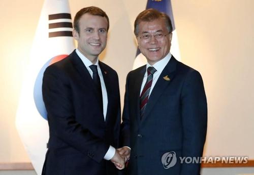 握手を交わす文大統領(右)とマクロン大統領=(聯合ニュース)