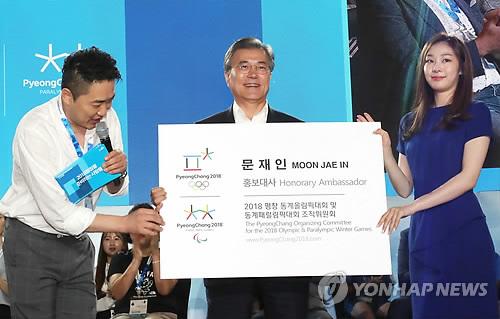 キム・ヨナさん(右)から広報大使の名刺を受け取った文大統領=24日、平昌(聯合ニュース)