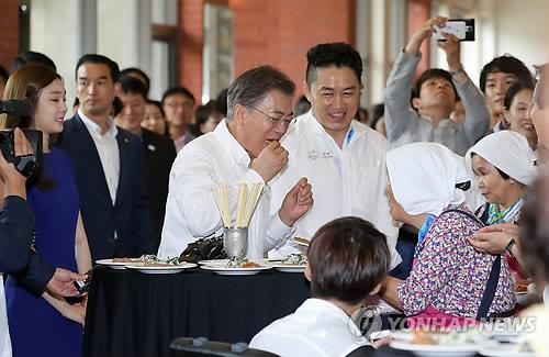 イベントで五輪開催地の郷土料理を味わう文大統領(中央)=24日、平昌(聯合ニュース)