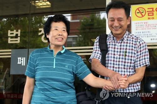 判決を受けて地裁前で笑顔を見せる原告の女性=8日、光州(聯合ニュース)