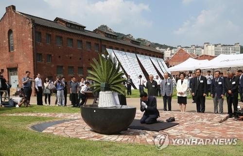 15年8月12日、追悼碑前でひざまずいて手を合わせる鳩山氏=(聯合ニュース)