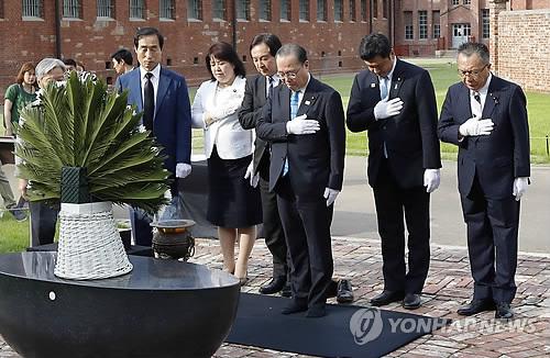 追悼碑前で黙とうを捧げる公明党の議員ら=8日、ソウル(聯合ニュース)