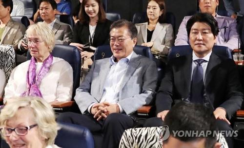 文大統領(中央)はソン・ガンホ氏(右端)やユルゲン・ヒンツペーター氏夫人と並んで映画を鑑賞した=13日、ソウル(聯合ニュース)