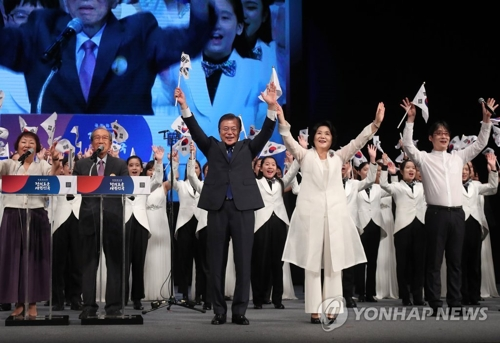 式典で万歳三唱する文大統領(前列左)と金正淑(キム・ジョンスク)夫人ら=15日、ソウル(聯合ニュース)