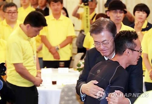 遺族の男性を抱擁する文大統領=16日、ソウル(聯合ニュース)
