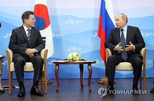 会談を行う文大統領(左)とプーチン大統領=6日、ウラジオストク(聯合ニュース)