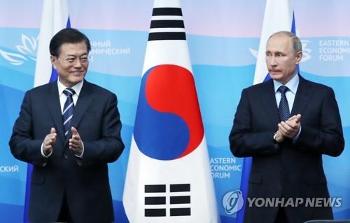 共同記者会見の会場で拍手をする文大統領(左)とプーチン大統領=6日、ウラジオストク(聯合ニュース)