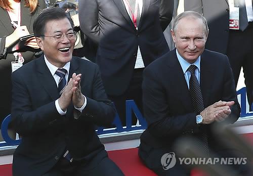 会談後、ウラジオストクの市内を散歩する文大統領(左)とプーチン大統領=6日、ソウル(聯合ニュース)
