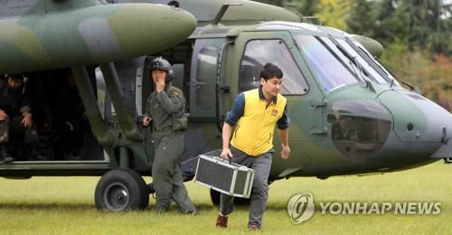 採取した試料を運ぶ韓国原子力安全委員会の関係者=6日、大田(聯合ニュース)