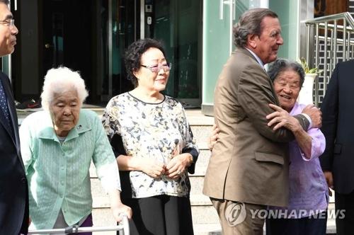 慰安婦被害者と抱き合うシュレーダー氏=11日、広州(聯合ニュース)