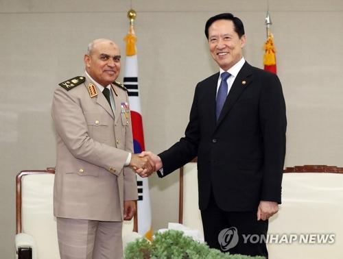 ソブヒ国防相(左)と握手する宋国防部長官=11日、ソウル(聯合ニュース)
