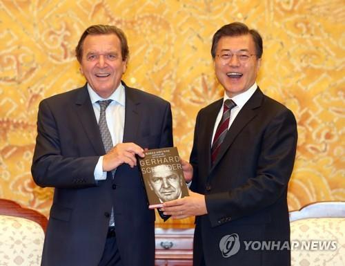 シュレーダー氏(左)から自伝を贈られ笑顔を見せる文大統領=12日、ソウル(聯合ニュース)