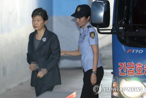 公判に出席するため、護送バスを降りてソウル中央地裁に向かう朴被告=12日、ソウル(聯合ニュース)