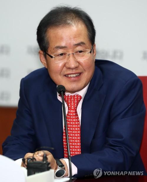 党本部で記者会見を行う洪代表=13日、ソウル(聯合ニュース)