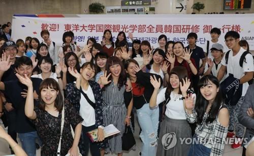 空港で記念撮影する研修団=13日、ソウル(聯合ニュース)