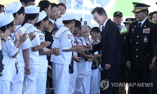 式典に参加した生徒らと握手する文大統領=13日、仁川(聯合ニュース)