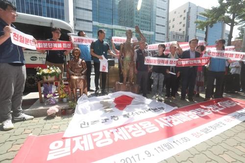少女像のそばに設置された労働者像のレプリカ=18日、釜山(聯合ニュース)