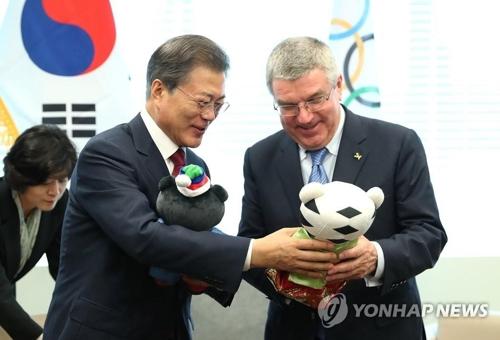 バッハ会長(右)に平昌五輪のマスコットをプレゼントする文大統領=(聯合ニュース)