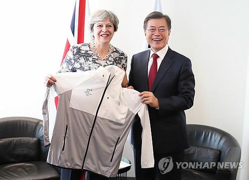 文大統領(右)はメイ首相との会談で、平昌五輪のユニフォームをプレゼントした=19日、ニューヨーク(聯合ニュース)
