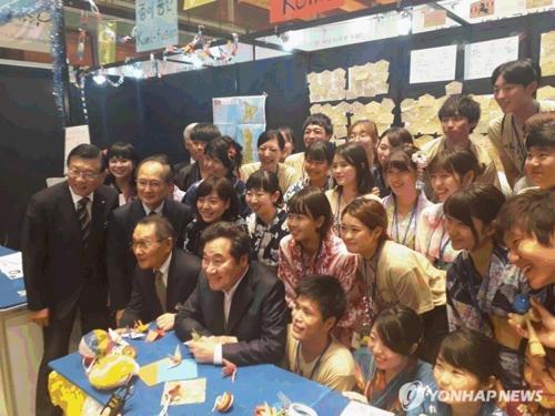 会場で日本の大学生と記念撮影する李首相(最前列左から2人目)=24日、ソウル(聯合ニュース)