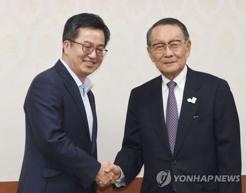 握手を交わす金副首相(左)と佐々木会長(企画財政部提供)=26日、ソウル(聯合ニュース)